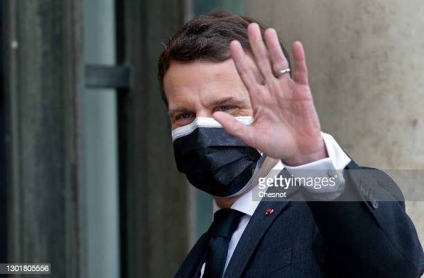 French President Emmanuel Macron wearing a protective face mask gestures as he welcomes President of Djibouti Ismail Omar Guelleh prior to a working...