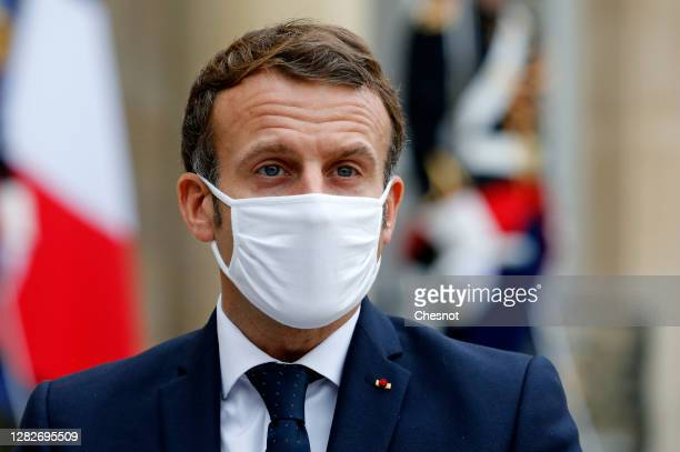 French President Emmanuel Macron wearing a protective face mask looks on as he makes a statement next to Estonian Prime Minister Juri Ratas following...