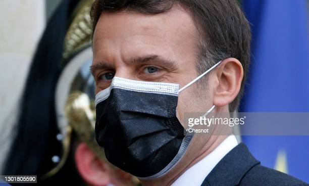 French President Emmanuel Macron wearing a protective face mask looks on as he welcomes President of Djibouti Ismail Omar Guelleh prior to a working...