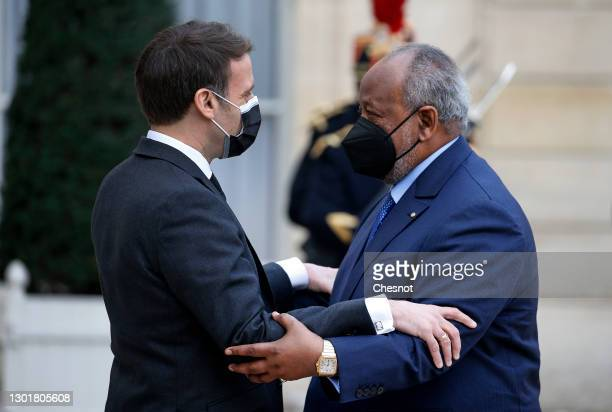 French President Emmanuel Macron wearing a protective face mask welcomes President of Djibouti Ismail Omar Guelleh prior to a working lunch at the...