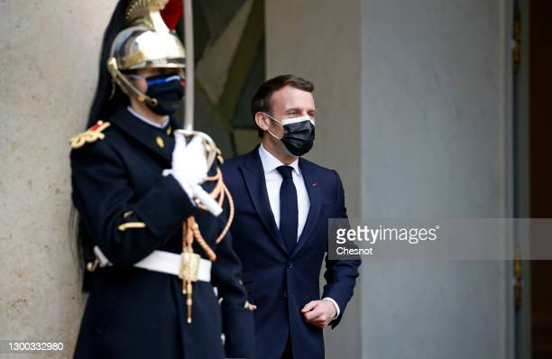 French President Emmanuel Macron wearing a protective face mask waits for Moldovan President Maia Sandu prior to a working lunch during an official...