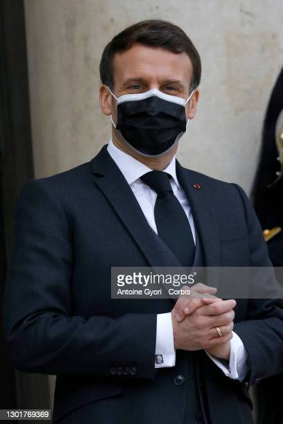 French President Emmanuel Macron, wearing a protective face mask, waits for Djibouti's President Ismail Omar Guelleh prior to a working lunch at the...