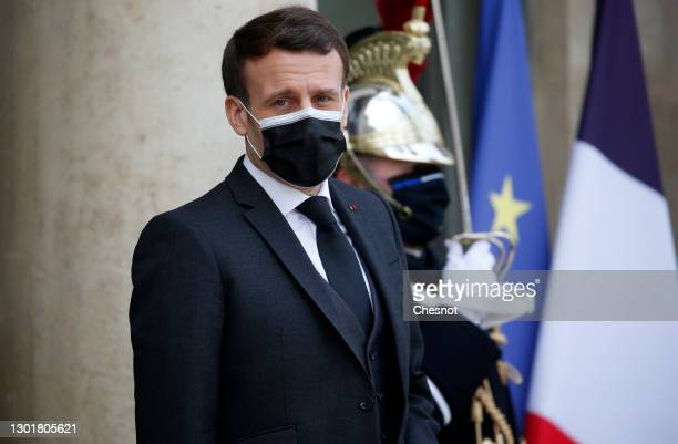 French President Emmanuel Macron wearing a protective face mask waits for President of Djibouti Ismail Omar Guelleh prior to a working lunch at the...
