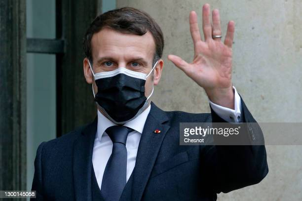 French President Emmanuel Macron wearing a protective face mask waves as he welcomes Slovakia's Prime Minister Igor Matovic prior to a working lunch...