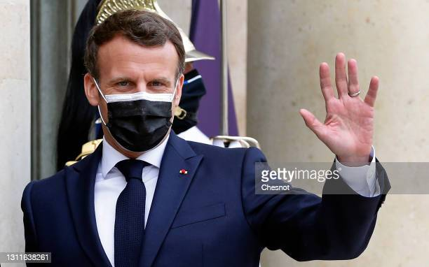 French President Emmanuel Macron wearing a protective face mask waves to media prior to his working lunch with Togolese President Faure Essozimna...