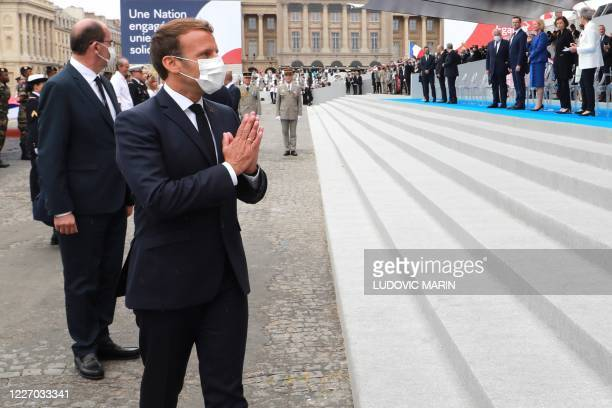 TOPSHOT French President Emmanuel Macron wearing a protective facemask greets guests at the end of the annual Bastille Day military ceremony on the...