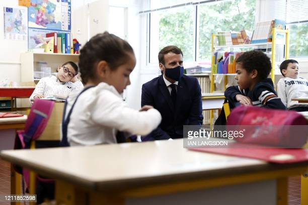 French President Emmanuel Macron wearing a protective mask speaks with pupils during a visit at the Pierre Ronsard elementary school in Poissy, west...