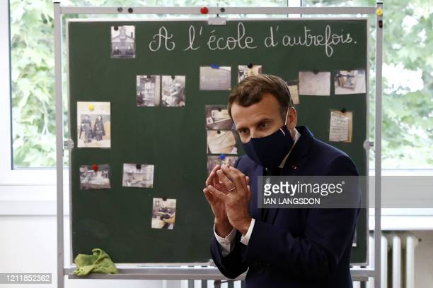 French President Emmanuel Macron wearing a protective mask with a blue-white-red colored ribbon speaks with pupils during a visit at the Pierre...