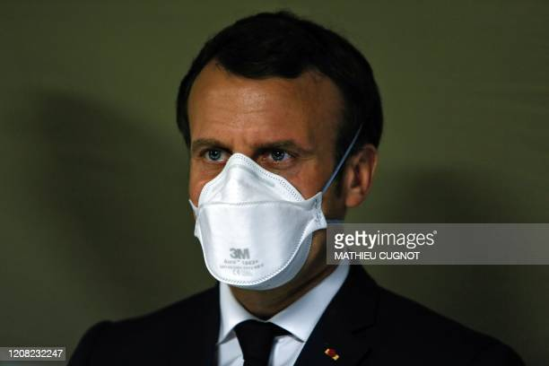 TOPSHOT French President Emmanuel Macron wears a face mask during the visit of the military field hospital outside the Emile Muller Hospital in...