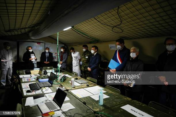 French President Emmanuel Macron wears a face mask during the visit of the military field hospital outside the Emile Muller Hospital in Mulhouse,...