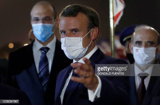 TOPSHOT French President Emmanuel Macron wears a mask due to the Covid19 pandemic as he gestures upon arrival at Beirut International airport on...
