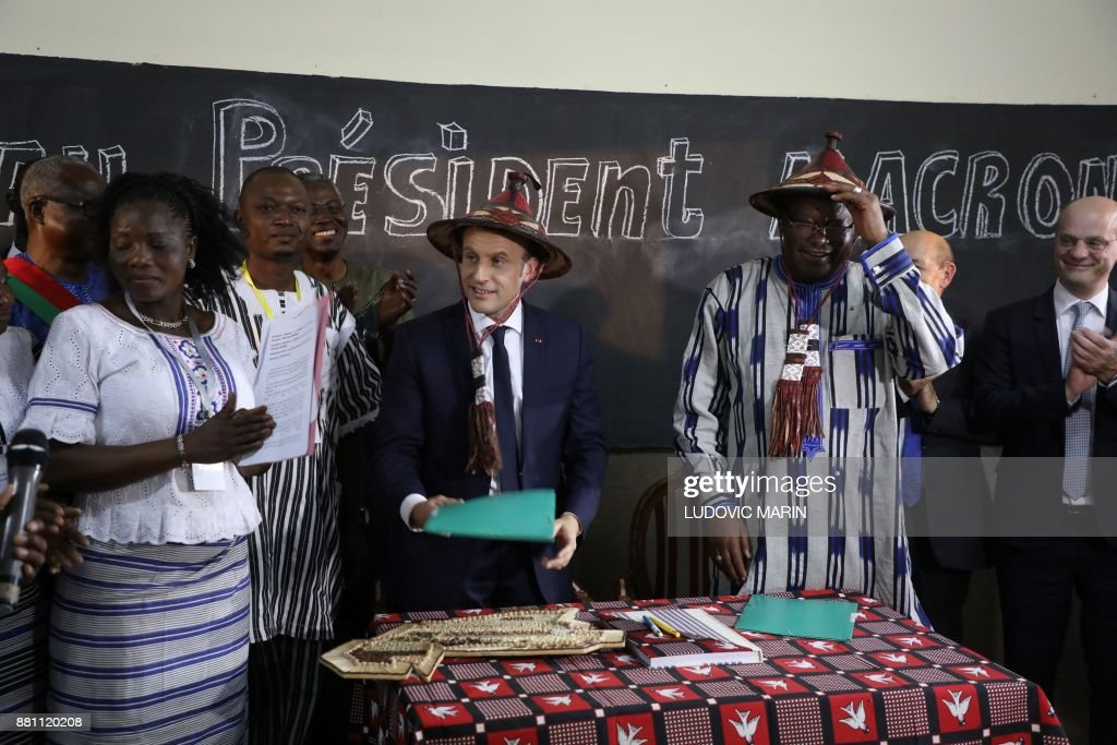 TOPSHOT - French President Emmanuel Macron (C) wears a traditional hat next to Burkina Faso's President Roch Marc Christian Kabore (2ndR) in a classroom as he visits the Lagm Taaba school on November 28, 2017, in Ouagadougou, as part of his first African tour since taking office. / AFP PHOTO / POOL / ludovic MARIN