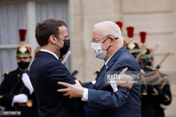 French President Emmanuel Macron weelcome the President of Israel Reuven Rivlin wearing protective face masks wave prior to their meeting at the...