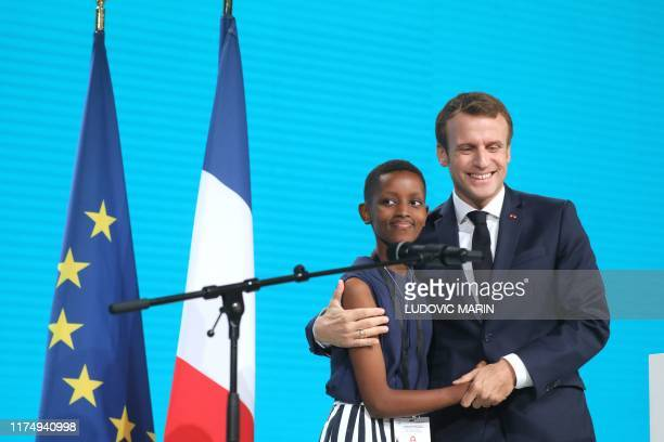 French President Emmanuel Macron welcomes Burundi's Amanda Dushime who comes to testify about her HIV sickness in Lyon, central eastern France, on...