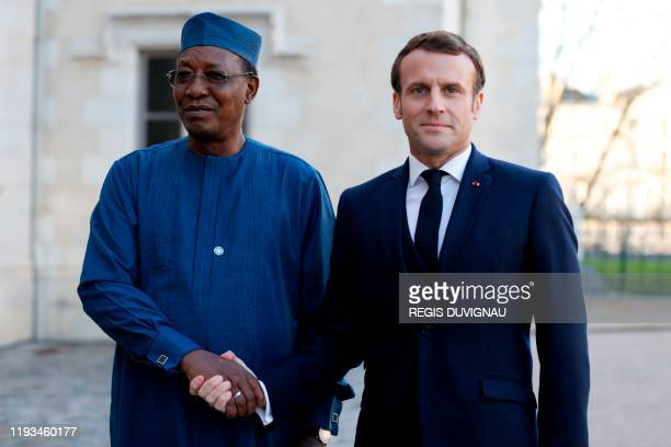 French President Emmanuel Macron welcomes Chad's President Idriss Deby during a summit on the situation in the Sahel region in the southern French...