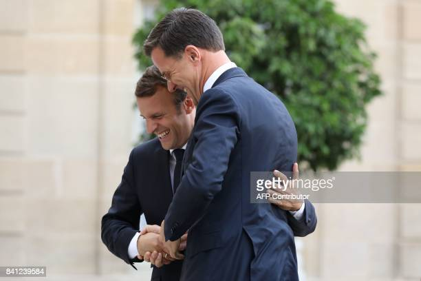 French president Emmanuel Macron welcomes Dutch Prime Minister Mark Rutte upon his arrival at the Elysee presidential palace for a meeting on August...