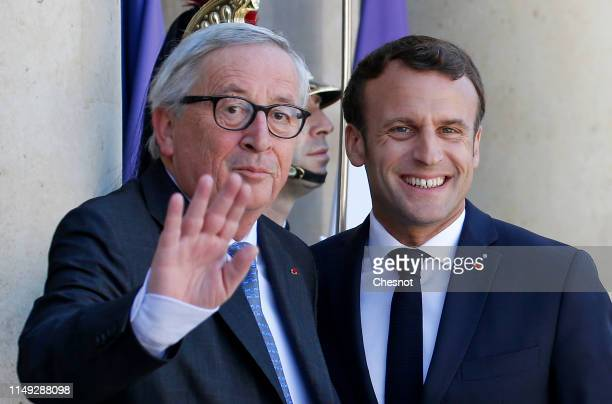 French President Emmanuel Macron welcomes European Commission President Jean-Claude Juncker prior to their meeting at the Elysee Palace on May 15,...