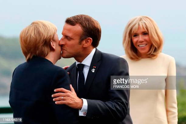 French President Emmanuel Macron welcomes German Chancellor Angela Merkel with a kiss past his wife Brigitte Macron at the Biarritz lighthouse,...