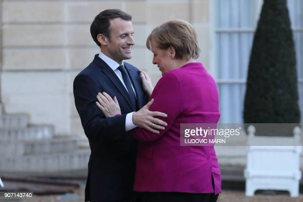TOPSHOT French president Emmanuel Macron welcomes German Chancellor Angela Merkel at the Elysee Palace in Paris on January 19 2018 / AFP PHOTO /...