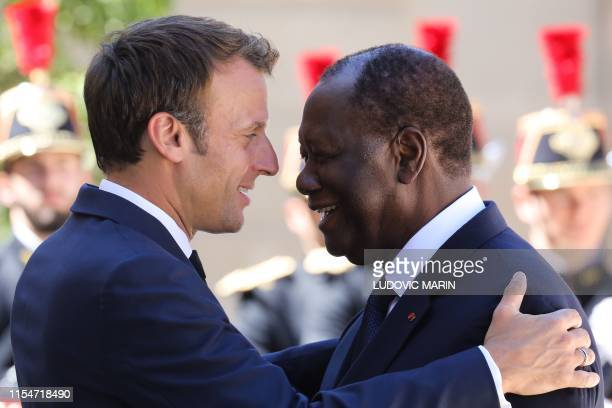 French President Emmanuel Macron welcomes Ivory Coast's President Alassane Ouattara at the Elysee palace, on July 9 ahead of a meeting, in Paris.