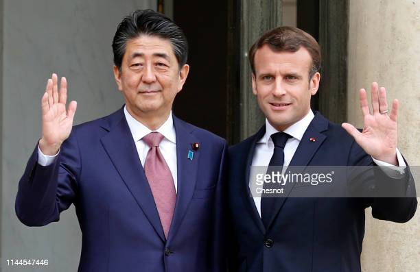 French President Emmanuel Macron welcomes Japanese Prime Minister Shinzo Abe prior to their meeting at the Elysee Presidential Palace on April 23...