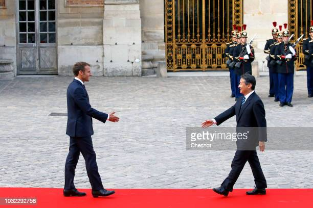 French President Emmanuel Macron welcomes Japan's Crown Prince Naruhito prior to their meeting at the Chateau de Versailles on September 12 2018 in...