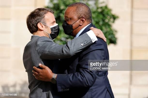 French President Emmanuel Macron welcomes Kenya's President Uhuru Kenyatta before their meeting at the Elysee presiential Palace in Paris on July 1,...