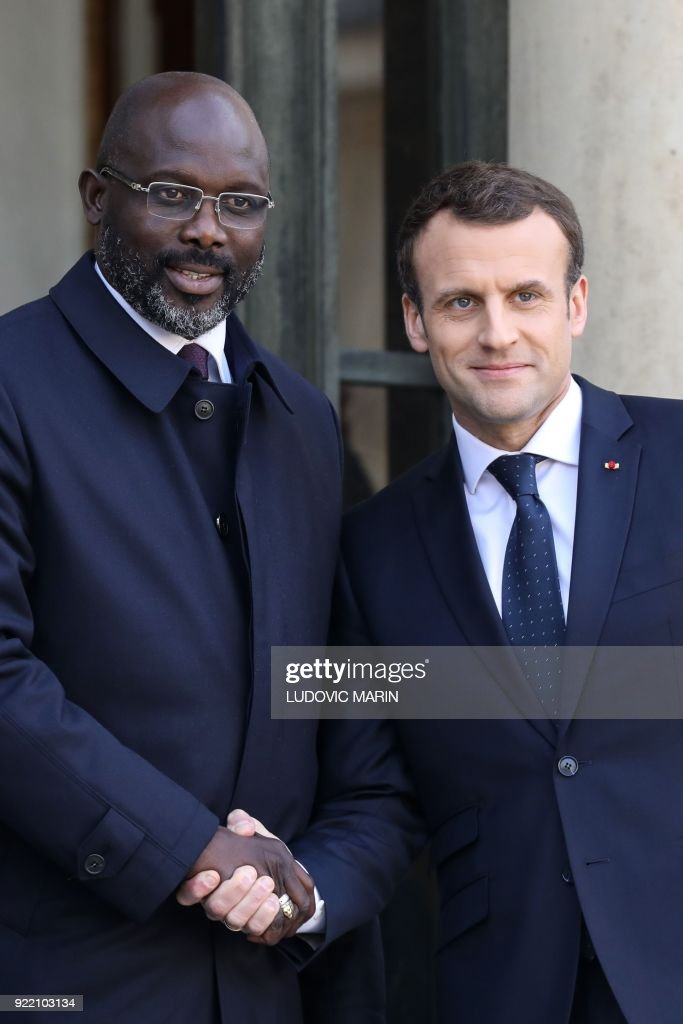 French President Emmanuel Macron (R) welcomes Liberian President George Weah, upon his arrival at the Elysee presidential palace for a lunch on February 21, 2018, in Paris. /