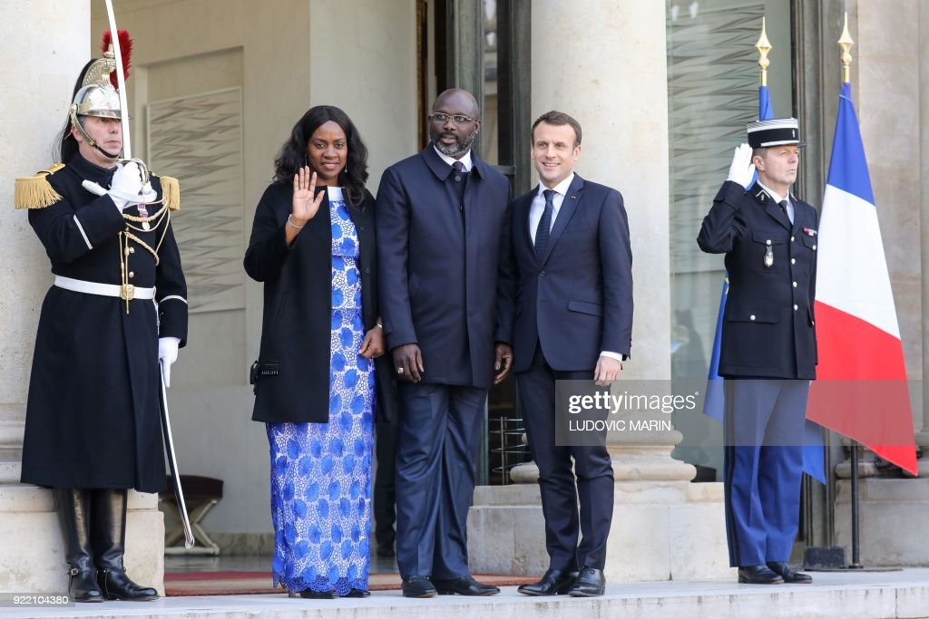 French President Emmanuel Macron (R) welcomes Liberian President George Weah (C) and his wife Clar, upon their arrival at the Elysee presidential palace for a lunch on February 21, 2018, in Paris