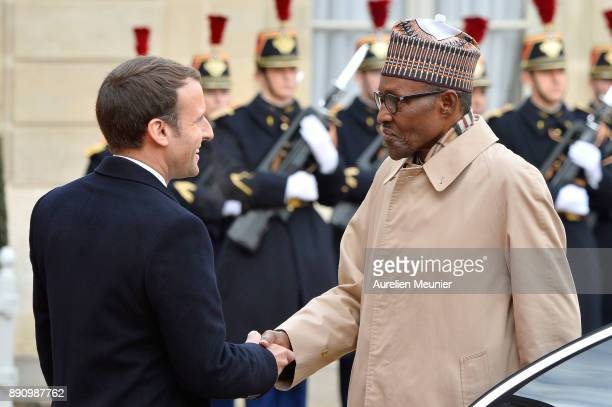 French President Emmanuel Macron welcomes Nigerian President Muhammadu Buhari as he arrives for a meeting for the One Planet Summit's international...