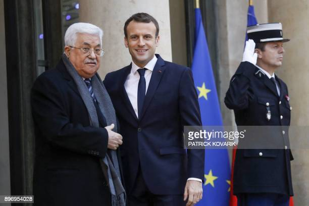 French president Emmanuel Macron welcomes Palestinian President Mahmud Abbas upon his arrival at the Elysee presidential palace in Paris for a...