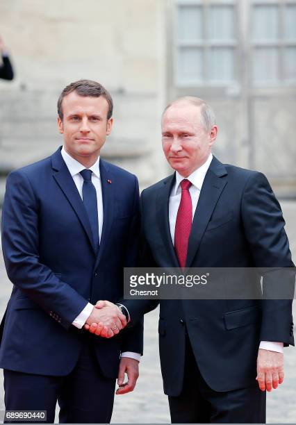 French President Emmanuel Macron welcomes Russian President Vladimir Putin prior to their meeting at 'Chateau de Versailles' on May 29 2017 in...