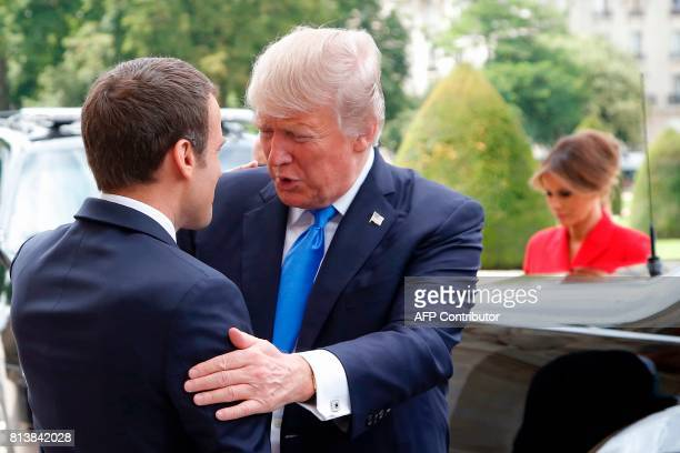 French President Emmanuel Macron welcomes US President Donald Trump next to US First Lady Melania Trump outside the Army Museum during a ceremony at...
