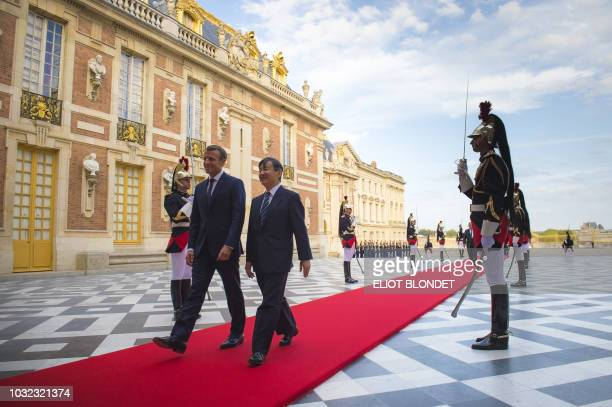 French President Emmanuel Macron welcones Japan's Crown Prince Naruhito in the Cour Royale of the Chateau de Versailles castle before an official...