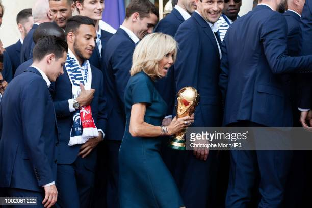 French President Emmanuel Macron's wife Brigitte Macron holds the trophy at a reception for the French national football team after they won the...