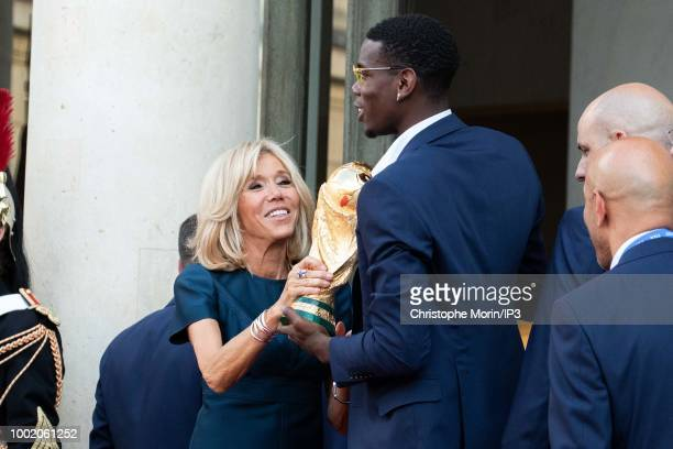French President Emmanuel Macron's wife Brigitte Macron holds the trophy next to France's midfielder Paul Pogba at a reception for the French...