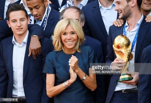 French President Emmanuel Macron's wife Brigitte Macron smiles next to France's goalkeeper Hugo Lloris holding the trophy and France's forward...