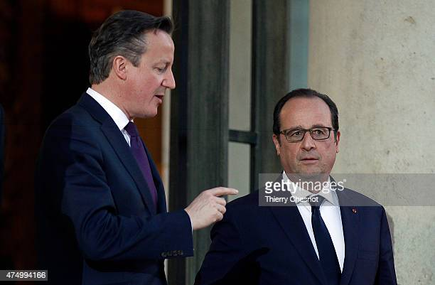 French President Francois Hollande accompanies British Prime Minister David Cameron after their meeting at the Elysee Palace on May 28 2015 in Paris...