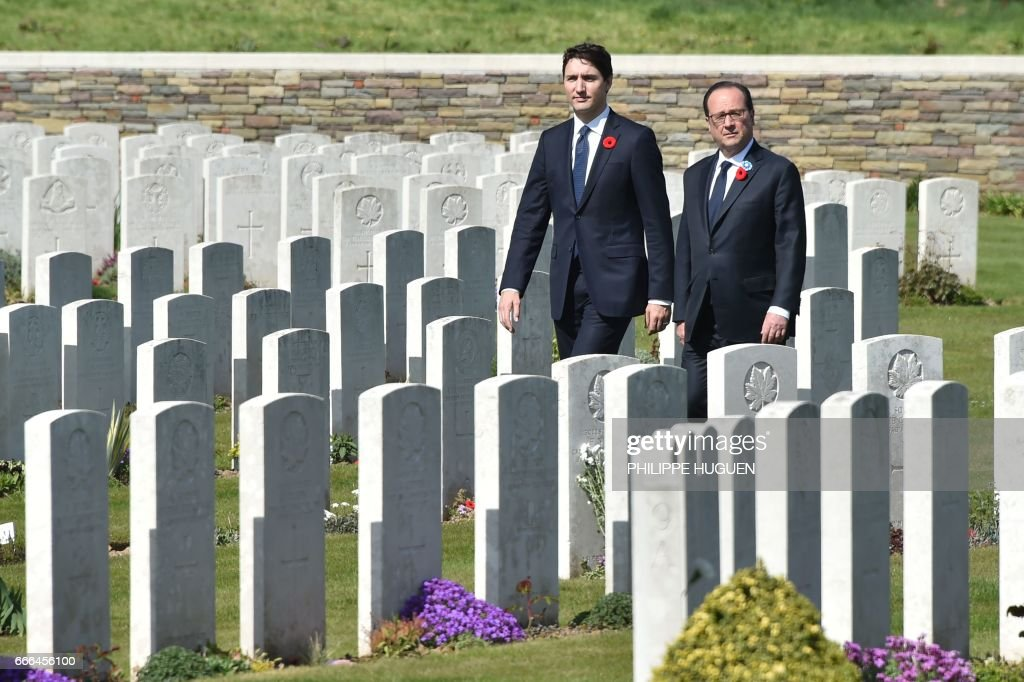 TOPSHOT - French President Francois Hollande (R) and Canadian Prime Minister Justin Trudeau walk in the Canadian WWI military cemetery in Vimy, near Arras, northern France, on April 9, 2017, during a commemoration ceremony to mark the 100th anniversary of the Battle of Vimy Ridge, a World War I battle which was a costly victory for Canada, but one that helped shape the former British colony's national identity. / AFP PHOTO / POOL AND AFP PHOTO / Philippe HUGUEN