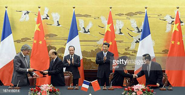 French President Francois Hollande and Chinese President Xi Jinping applaud as agreements are exchanged during a signing ceremony between China and...