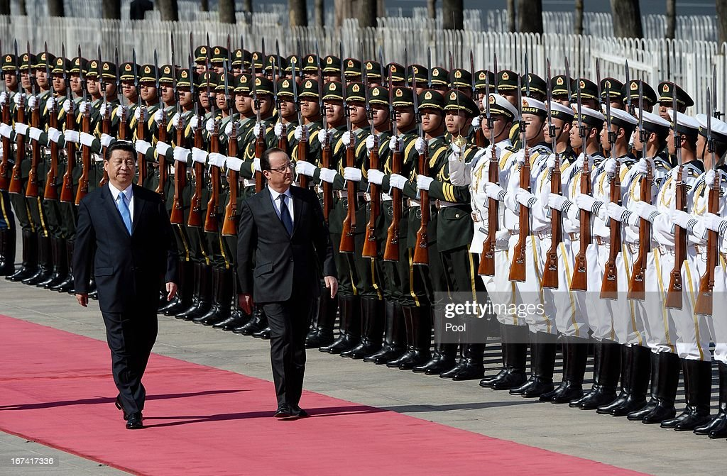 French President Francois Hollande (R) and Chinese President Xi Jinping inspect a guard of honor during a welcomingceremony outside the Great Hall of the People on April 25, 2013 in Beijing, China. Hollande has begun a two day trade visit to China bringing with him a large French trade delegation.