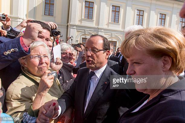 French President Francois Hollande and German Chancellor Angela Merkel greet well-wishers after a ceremony to mark a watershed 1962 speech by Charles...