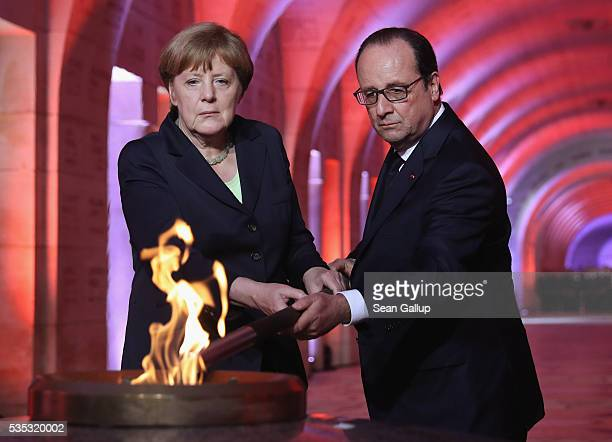 French President Francois Hollande and German Chancellor Angela Merkel light an eternal flame inside the ossuary at Douaumont in memory of the 130000...