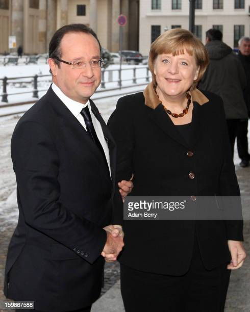 French President Francois Hollande and German Chancellor Angela Merkel arrive at the French embassy in front of the Brandenburg Gate during the 50th...