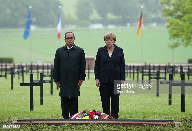 French President Francois Hollande and German Chancellor Angela Merkel stand at a memorial after laying a wreath at the German World War I military...