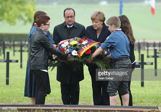 French President Francois Hollande and German Chancellor Angela Merkel lay a wreath together with French and German children at the German World War...