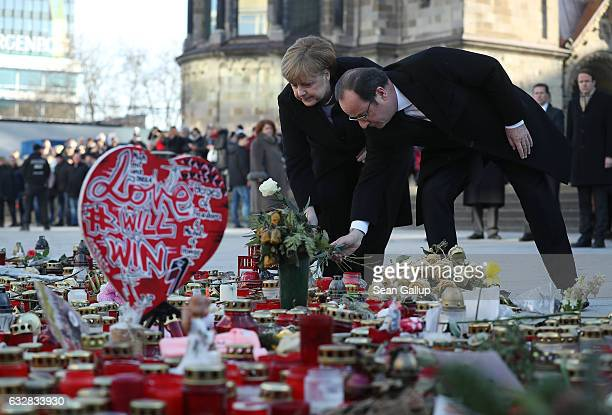 French President Francois Hollande and German Chancellor Angela Merkel lay flowers at a memorial to the victims of the December Berlin terror attack...