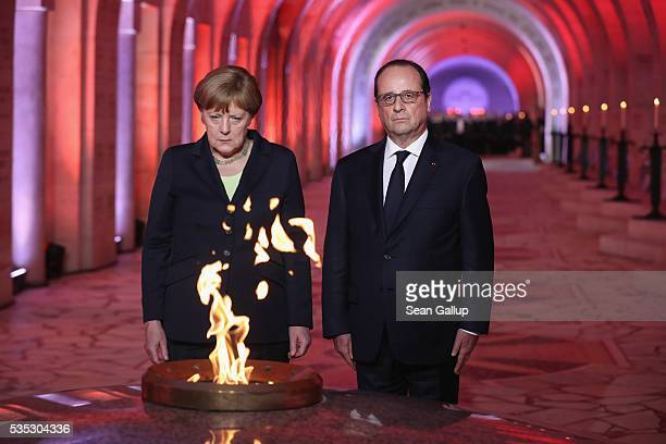 French President Francois Hollande and German Chancellor Angela Merkel look on after lighting an eternal flame inside the ossuary at Douaumont in...