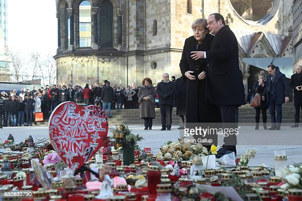 French President Francois Hollande and German Chancellor Angela Merkel pause after laying flowers at a memorial to the victims of the December Berlin...