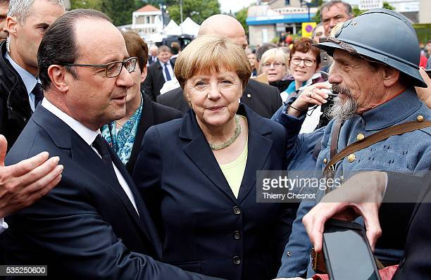 French President Francois Hollande and German Chancellor Angela Merkel talk with a history reenactor dressed as World War I French soldier during...